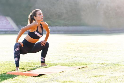 Girl in sportswear doing workout burning fat calories training strength practicing effort domestic fitness females aerobics sport fit on stadium. Sports. Activity. Motivation. Confidence.
