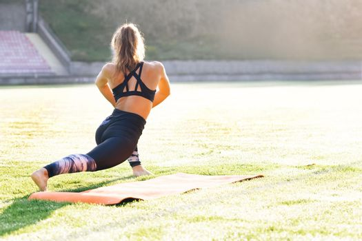 Young caucasian fit sport woman stretching her body warm up before workout outdoor. The girl in sportswear exercises outside in the morning sun for health and wellbeing
