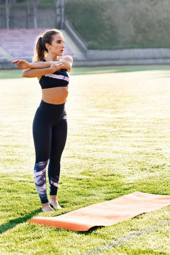 Sports. Activity. Motivation. Woman in sportswear doing workout burning fat calories training strength practicing effort domestic fitness females aerobics sport fit on stadium. Confidence.