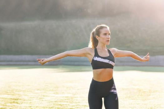 New normal sport outdoor young caucasian fit sport woman stretching her body warm up before workout outdoor. The girl in sportswear exercises outside in the morning sun for health and wellbeing