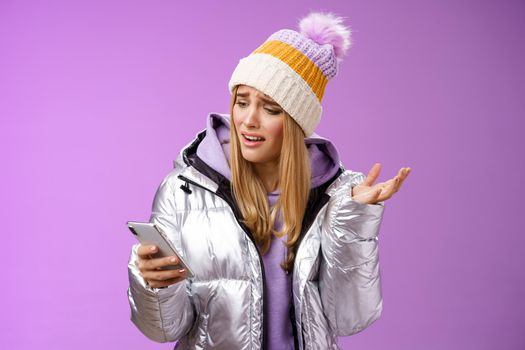 Upset disappointed attractive whining gloomy blond girl in silver jacket standing outside hat holding smartphone shrugging raising hand dismay complaining slow mobile internet, purple background