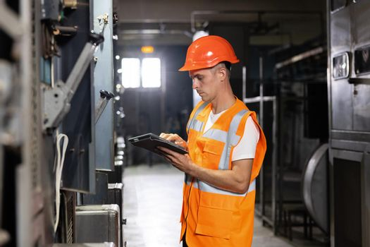 Engineer male working at factory. Electrical engineer using digital tablet inspect and program for electric power system in electrical control room. Concept of industry, factory, renewable energy