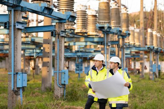 Engineers in special clothing discuss a drawing on paper near high-voltage power line. Engineers men in warm clothes use construction plan discuss work walking against power electric station