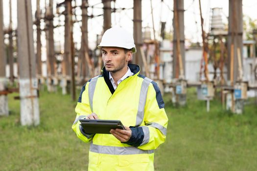 Male engineer in uniform and helmet standing outdoor and tapping on tablet. Man standing near high voltage substation and typing on device