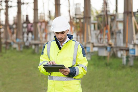 Man standing near high voltage substation and typing on device. Male engineer in uniform and helmet standing outdoor and tapping on tablet