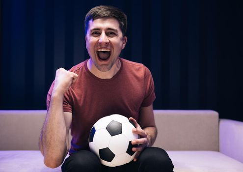 Young fun guy 30s football fan cheer up support favorite team hold soccer in red t-shirt in dark living room. People emotions sport leisure lifestyle concept