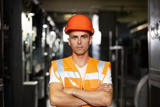 Portrait of an engineer man or worker crossing arms, working in electrical room station. Power energy motor machinery cabinets in control or server room, operator station network in industry factory