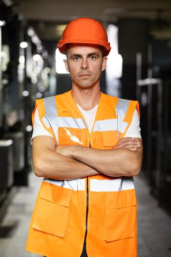 Power energy motor machinery cabinets in control or server room, operator station network in industry factory. Portrait of an engineer man or worker crossing arms, working in electrical room station