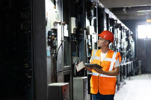 Engineer man or worker, people working in electrical station. Power energy motor machinery cabinets in control or server room, operator station network and circuit center in industry factory system