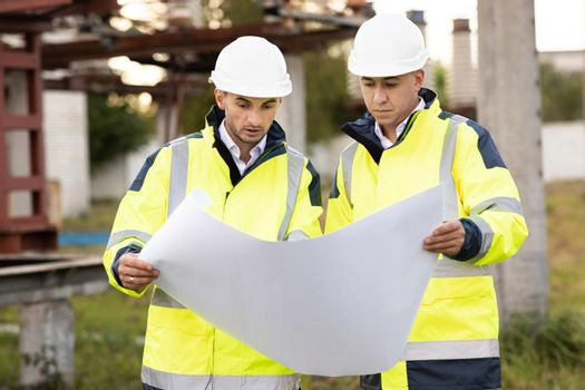 Two engineers are talking in front of electrical transmission lines, working on renewable energy development. Engineers in special clothing discuss a drawing on paper near high-voltage power line