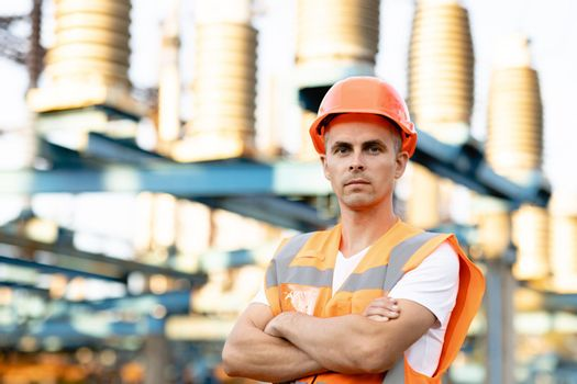 Portrait of engineer worker in uniform and helmet standing near high voltage substation with tall pylons and voltage distribution cables