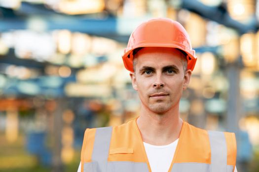 Close up portrait of engineer worker in uniform and helmet standing near high voltage substation with tall pylons and voltage distribution cables
