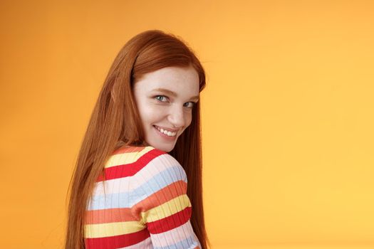 Tenderness, romance, seduction concept. Attractive cheeky flirty young redhead daring girl turn behind look shoulder camera smiling silly coquettish giggle express sympathy affection