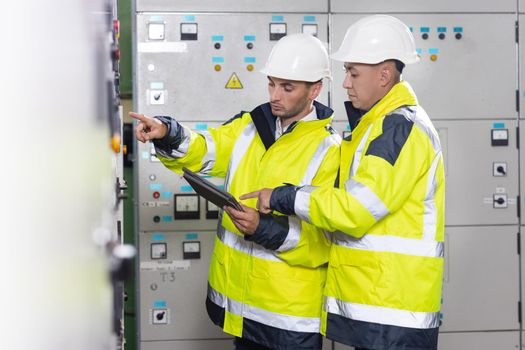 Electrical engineers checking control panel board with tablet. High voltage power station. Electrical engineers standing near therminal box of solar panel