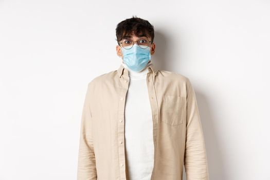 Young man in sterile medical mask from covid-19 looking surprised at camera, standing on white background. Coronavirus, quarantine and social distancing concept