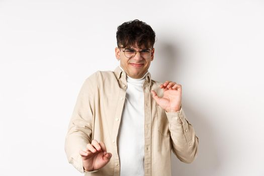 Disgusted guy grimacing and jumping away from something nasty, stare with aversion and dislike, rejecting bad offer, standing on white background