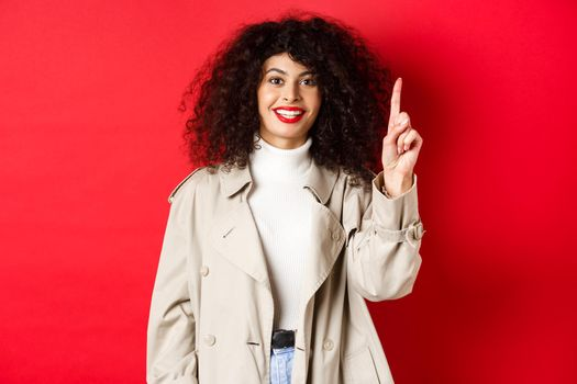 Attractive modern woman with red lips, curly hairstyle, wearing spring trench coat, pointing finger up and smiling, standing against red background