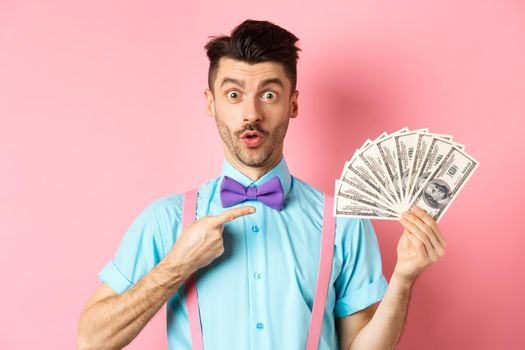 Amazed man showing big money prize, pointing at dollars and say wow, stare impressed at camera, standing over pink background