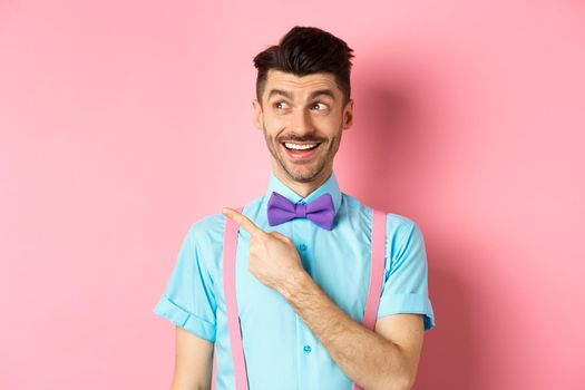 Cheerful caucasian man in funny bowtie looking and pointing hand left, showing promo logo, standing on pink background