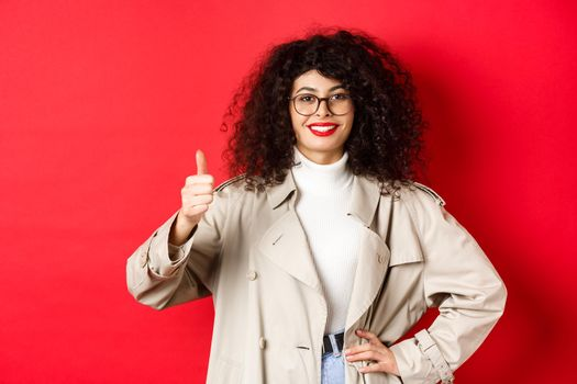Cheerful woman showing thumbs up and smiling, recommending good thing, standing in glasses and trench coat against red background