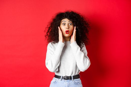 Surprised young woman hear amazing news, looking at promo and saying wow, stare with disbelief, standing on red background
