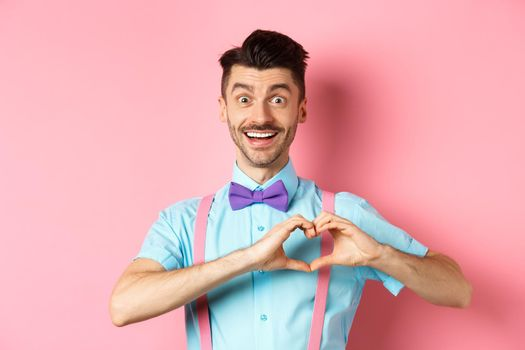 Passionate guy in funny bow tie saying I love you, showing heart gesture on Valentines day and smiling, expressing sympathy to lover, standing over pink background