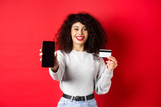 Happy good-looking girl showing plastic credit card and empty smartphone screen, demonstrate account or application, standing on red background