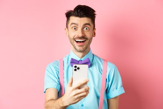 Image of excited man checking out promo offer online, holding smartphone and stare surprised at camera, standing happy on pink background