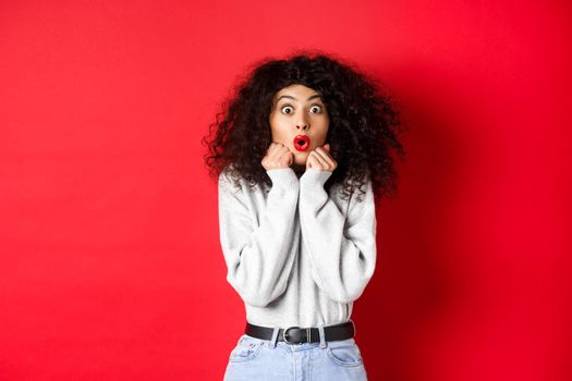 Surprised young woman looking with disbelief and amazement at camera, saying wow and standing in awe on red background
