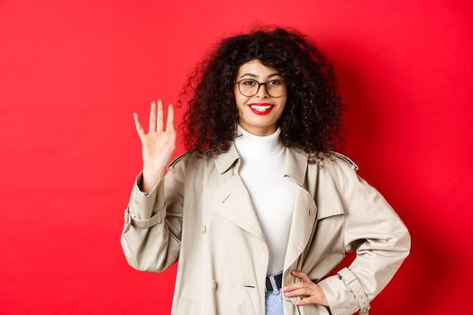Stylish european woman in glasses and trench coat, waiving hand and smiling, saying hello, greeting someone, standing on red background