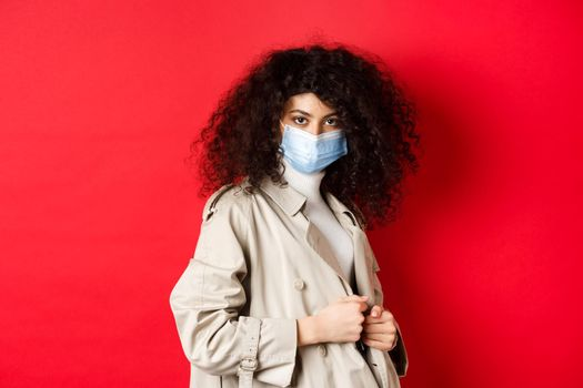 Covid-19, pandemic and quarantine concept. Sassy girl in trench coat and medical mask, put on trench coat for spring walk, red background