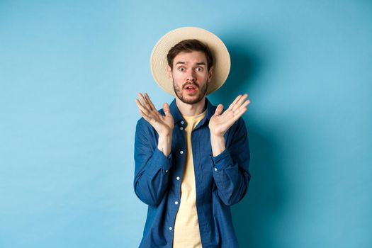Image of shocked tourist in straw hat panicking, raising hands up and stare startled at camera, standing on blue background