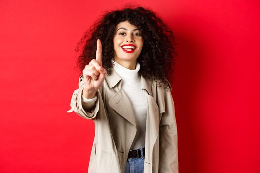 Cheerful woman in trench coat, showing number one finger and smiling, standing on red background