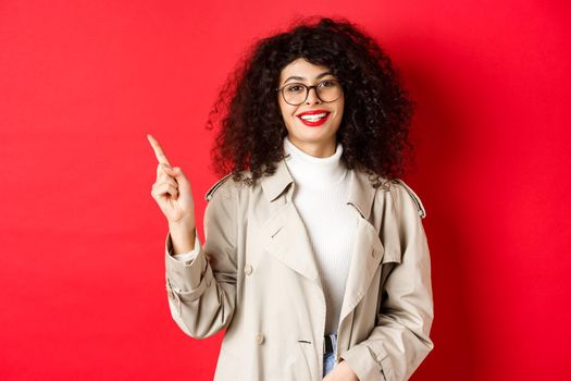 Portrait of stylish caucasian woman in trench coat and glasses pointing finger aside, showing empty space on red background and smiling