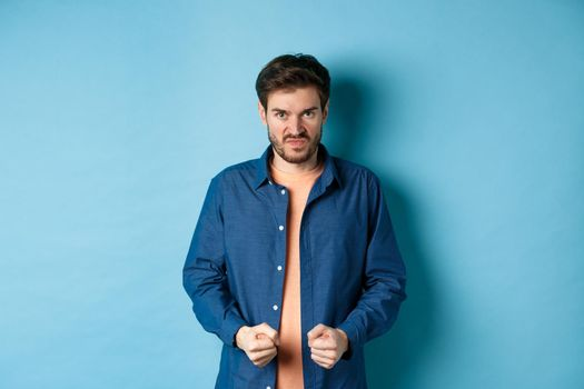 Angry and pissed-off man clench fists and stare with disdain at camera, trying to keep himself together, look with rage, standing on blue background