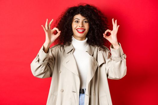 Stylish caucasian woman in trench coat showing okay gesture and smiling satisfied, recommending company, standing on red background