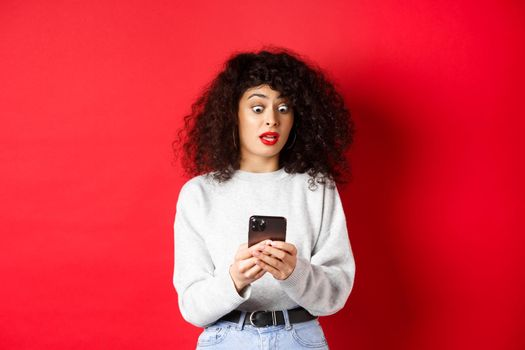 Shocked woman stare at smartphone screen with popped eyes, reading strange message, standing on red background