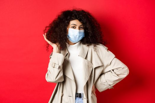 Covid-19, pandemic and quarantine concept. Stylish coquettish woman in medical mask and trench coat, fixing her curly hairstyle and smiling, red background