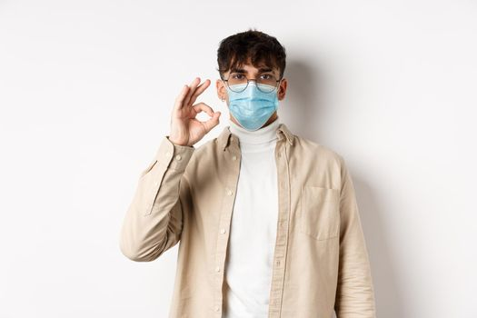 Covid-19, health and real people concept. Natural guy in glasses and medical mask show Ok sign, agree or approve something, standing on white background