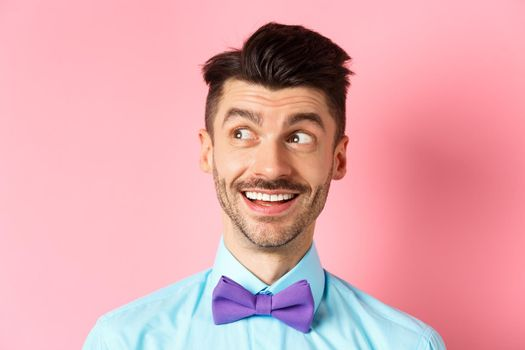 Close-up of amused smiling guy with moustache, pointing and looking left happy, stare at logo, standing on pink background