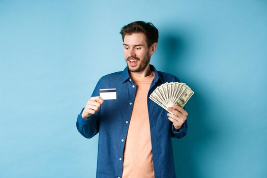 Handsome young man showing cash and looking at plastic credit card, prefer contactless payment, standing on blue background
