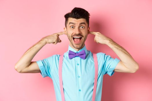 Childish funny guy shut ears and laughing at camera, refuse to listen, standing ignorant on pink background