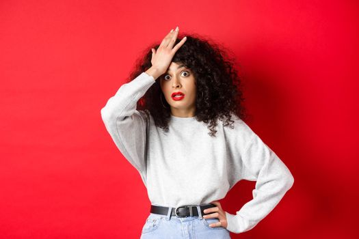 Annoyed and tired young woman slap forehead, making facepalm and stare at camera shocked, standing bothered against red background