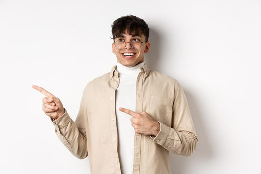 Excited and enthusiastic young man in glasses, pointing fingers and looking left with happy smile, standing in awe on white background
