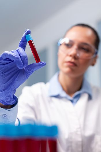 Specialist woman doctor looking at clinical vacutainer dna blood analyzing biology expertise