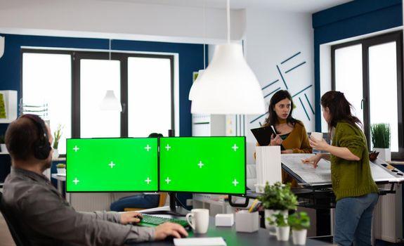 Employee with headphones working in dual monitror setup with green screen