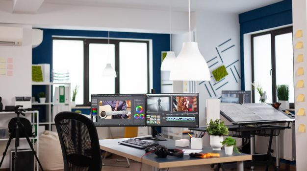 Empty modern creative agency office with dual monitors setup