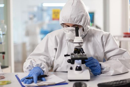 Scientist working to discover virus vaccine dressed in ppe suit