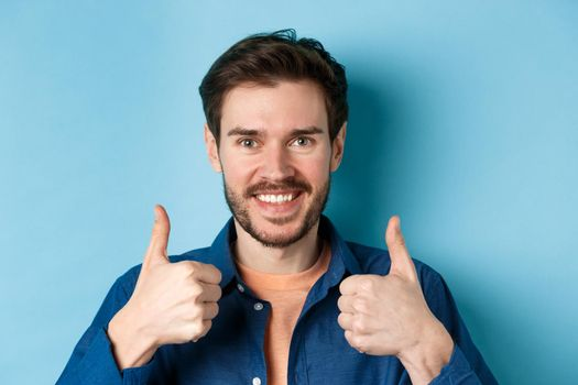Close-up of smiling good-looking man showing thumbs up, praising good job, recommending company, standing on blue background