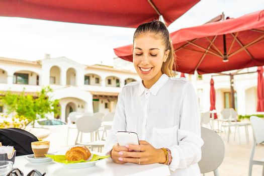 Cute holded hair girl in white shirt smiling using smartphone taking breakfast at hotel cafe garden. Millennial hipster woman using technology sitting at dehors table with croissant and cappuccino